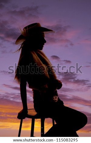 A silhouette of a woman sitting on a stool with the wind blowing her hair.