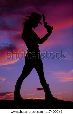 A silhouette of a woman standing and holding a weapon.