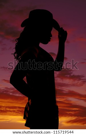 a silhouette of a woman touching the brim of her hat with a beautiful  colorful sky behind her.