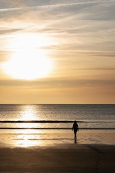 A silhouette of a woman walking on a black beach during sunset. The photo is taken in Akranes in Iceland   where swimming in the sea is popular all year around.