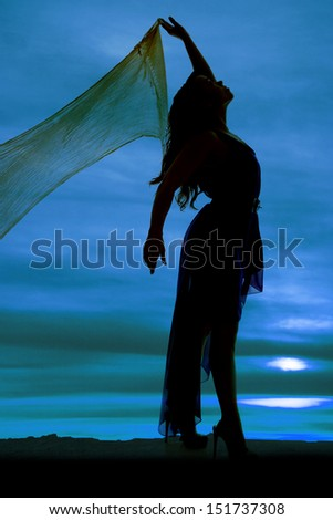 a silhouette of a  woman with her sarong holding it up and dancing.