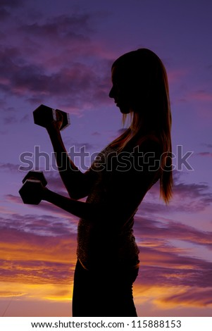 a silhouette of a woman working out with weights with a colorful sky in the background.