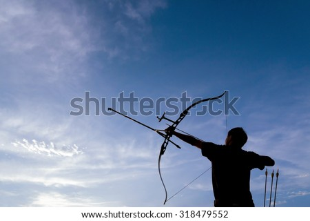 A silhouette of an archer drawing his bow and aiming upwards with deep blue sky and white clouds as background