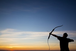 A silhouette of an archer firing an arrow towards a colorful morning sky with beautiful gradient