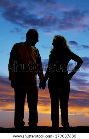 a silhouette of an elderly couple holding hands in the outdoors.