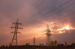 A silhouette of high voltage power lines against a colorful sky at sunrise or sunset.