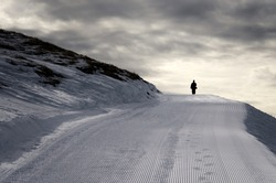 A silhouette of one man walking alone on the snowy mountain path, winter in the mountains, moody landscape