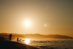 A silhouette of people walking on the shore near the water with mountain and clear sky in the background