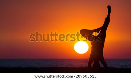 A silhouette of the man practicing yoga outdoors (at the seashore) at the sunset.