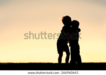 A silhouette of two little boys, a young child and his toddler brother, hugging at sunset.