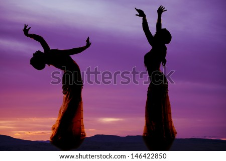 A silhouette of two women belly dancing.