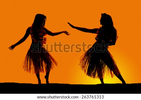 A silhouette of two women dancing in their grass skirts, in the outdoors.
