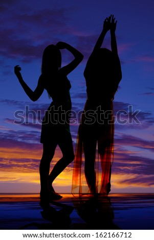 A silhouette of two women dancing together.
