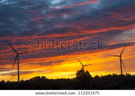 A silhouette of windturbines on a amazing sunset