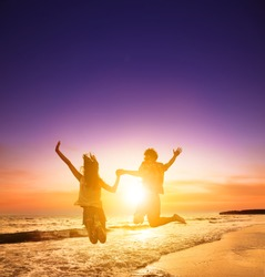 A silhouette of young couple jumping on the beach