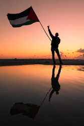 A Silhouette photo of youth, holding up Palestinian flag near Gaza beach. Gaza - Palestine