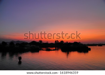 a silhouette shot of river with reflection and orange twilight sky