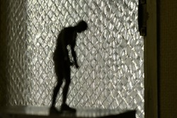 A silhouetted figure stands in front of a window. Figured is blurred and abstract. feeling of isolation and anxiety.