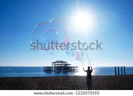 A silhouetted man standing on brighton beach with a bubble wand a big big bubble from the wand is floating in the sky, behind is Brighton's West Pier, the sky is bright blue behind