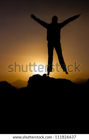 A silhouetted person jumping in front of the rising desert sun