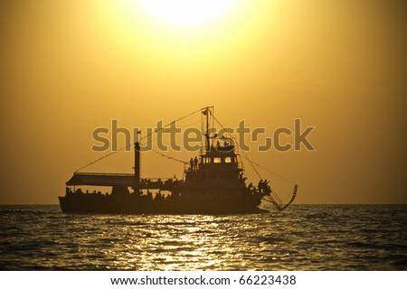 a silhoutte of a ship at sunset