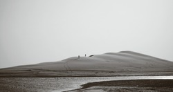 A silhuette of 2 strangers climbing on the edge of the huge sand dune in desert in Qatar (a boarder with saudi arabia), black and white photo