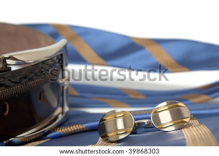 A silk tie, leather belt and cufflinks are posed on a nutral background. The image suggests the end of a hard days work, relaxation, or preparation for work.