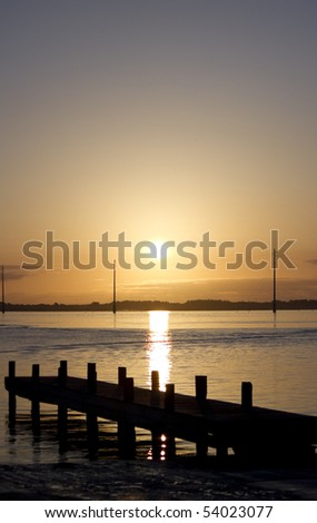 a silouehette of a small pier during sunrise on the shore of Florida