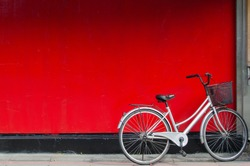 A silver bike parking in front of a red wall.