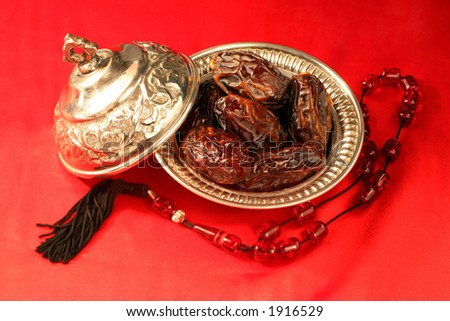 A silver bowl containing the finest dates which are traditionally eaten in Arabia for Iftar to break the Ramadan fast at sundown next to prayer beads.