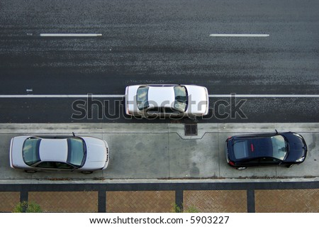 A silver car stopped on the road between two parked cars preparing to parallel park against curb.