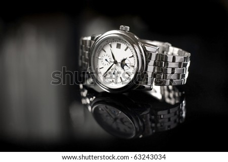 A silver coloured stainless steel watch for men on a reflective black background.
