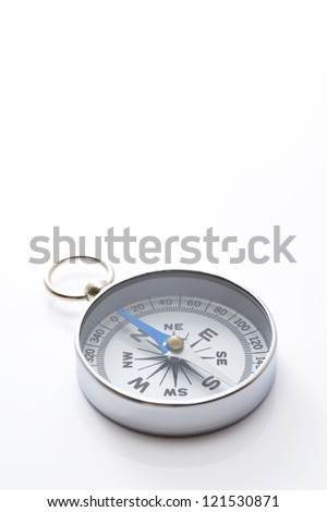 a silver compass on gray background, close-up