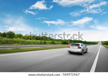 A silver crossover car driving fast on the countryside asphalt road against blue sky with white clouds