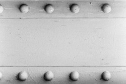 A silver painted metal background texture with four rusted bolts or rivets.