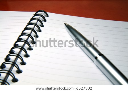 A silver pen on a blank page of notebook.