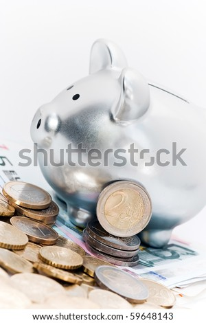 A silver piggy or savings bank surrounded by Euro notes and coins.  White background