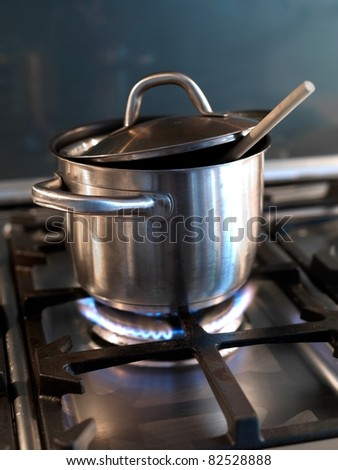 A  silver pot on a cook top under heat