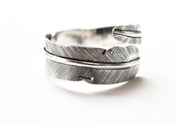 A silver ring in the style of a feather