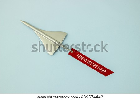 A silver toy airplane flying with removable tag of remove before flight