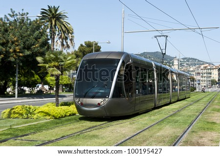 A silver tram on a grassy railway in Nice, France. - stock photo