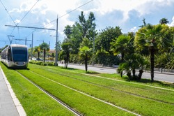 A silver tram running on rails surrounded by fresh green grass in city center in Nice, France.