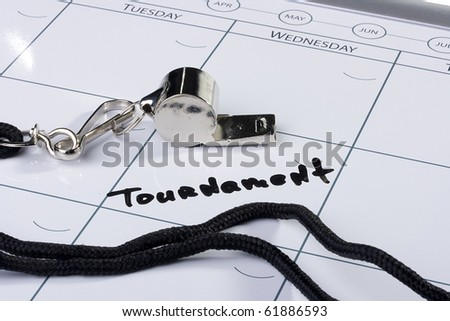 A silver whistle laying next to the word Tournament drawn on a calendar.