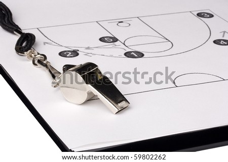 A silver whistle laying on a paper with the basketball game plan on it.