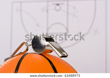 A silver whistle laying on an orange basketball in front of the game plan.
