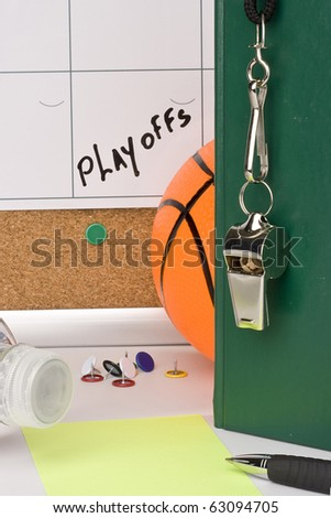 A silver whistle on a green notebook next to a basketball and a calendar with the date of the playoffs on it.