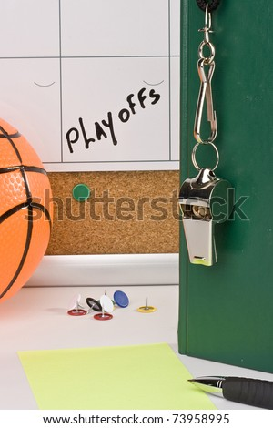 A silver whistle on a green notebook next to an orange basketball and a calendar with the date of the playoffs on it.
