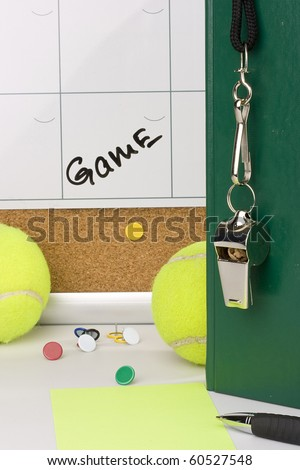A silver whistle on a green notebook next to tennis balls and a calendar with the date of the game on it.