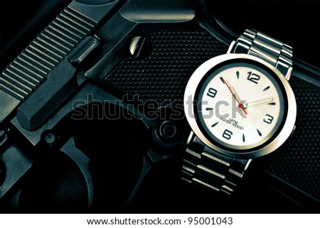 A silver wrist watch is placed on the hand grip of an automatic pistol.  There is a spy, agent, police or military theme.
