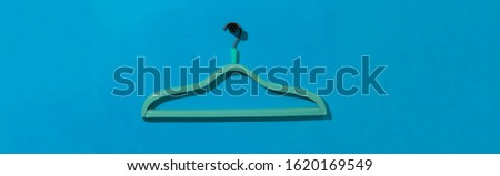 a simple empty clothes hanger on the wall hook, fashion cloth textile storage